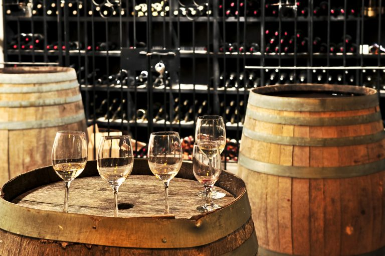 wine cellar with wine glasses on barrels